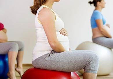 Mujer embarazada haciendo ejercicio con una pelota